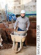 Купить «Worker carrying bucket with cement mortar on cart», фото № 33210358, снято 25 февраля 2020 г. (c) Яков Филимонов / Фотобанк Лори