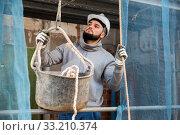 Купить «Worker lifting bucket with cement mortar», фото № 33210374, снято 25 февраля 2020 г. (c) Яков Филимонов / Фотобанк Лори