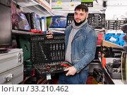 Focused man is choosing ratchet in store. Стоковое фото, фотограф Яков Филимонов / Фотобанк Лори