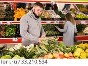 Купить «Adult man is choosing leek and celery in the grocery store», фото № 33210534, снято 20 ноября 2019 г. (c) Яков Филимонов / Фотобанк Лори