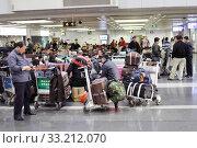 Купить «Пассажиры в зоне вылета международного аэропорта Пекина ждут свой рейс», фото № 33212070, снято 20 февраля 2012 г. (c) Александр Гаценко / Фотобанк Лори