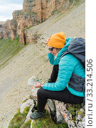 Купить «A traveler girl wearing a hat and sunglasses holds a hundred dollar bills in the hands of a fan against the backdrop of cliffs on nature. Keep your head from high cost.», фото № 33214506, снято 13 июля 2020 г. (c) easy Fotostock / Фотобанк Лори