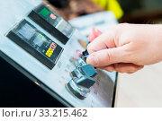Купить «A close-up of a man's hand holds a rotary switch on the equipment control panel with instruments..», фото № 33215462, снято 26 февраля 2020 г. (c) easy Fotostock / Фотобанк Лори