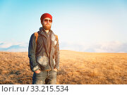 Portrait of a thoughtful stylish hipster with a beard in sunglasses and a hat with a backpack on the background of the snow-capped Mount Elbrus in the Caucasus at sunset. Стоковое фото, фотограф Zoonar.com/Ian Iankovskii / easy Fotostock / Фотобанк Лори