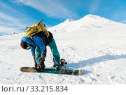 A snowboarder with a backpack on his back fastens snowboard bindings against the background of the Caucasian sleeping Elbrus volcano. North Caucasus. Стоковое фото, фотограф Zoonar.com/Ian Iankovskii / easy Fotostock / Фотобанк Лори