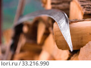 Купить «A hand braid for mowing grass and hay stands near the stacked firewood poked with an ax. Close-up», фото № 33216990, снято 30 мая 2020 г. (c) easy Fotostock / Фотобанк Лори