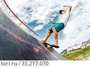 Купить «Teen skater hang up over a ramp on a skateboard in a skate park. Wide angle», фото № 33217070, снято 7 июля 2020 г. (c) easy Fotostock / Фотобанк Лори