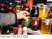 Wrinkled old women's hands hold a jar with homemade jam from coniferous leaves in the mountains. Стоковое фото, фотограф Zoonar.com/Ian Iankovskii / easy Fotostock / Фотобанк Лори