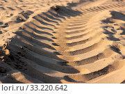 Купить «Fresh tracks in sand of a heavy construction vehicle are run into the distance. Tire tracks of a large vehicle in sand on a building area to road.», фото № 33220642, снято 9 июля 2020 г. (c) easy Fotostock / Фотобанк Лори