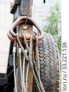 Купить «Metal ropes, hanging on its hinges behind the cab of a crane on a background of black tires», фото № 33221138, снято 4 апреля 2020 г. (c) easy Fotostock / Фотобанк Лори