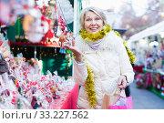 Positive mature female buying decoration at X-mas Fair. Стоковое фото, фотограф Яков Филимонов / Фотобанк Лори