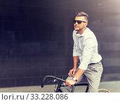 Купить «man with bicycle and headphones on city street», фото № 33228086, снято 21 августа 2016 г. (c) Syda Productions / Фотобанк Лори
