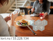 Купить «hands with phone and food nutritional value chart», фото № 33228134, снято 16 января 2017 г. (c) Syda Productions / Фотобанк Лори