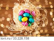 Купить «chocolate easter eggs in straw nest on table», фото № 33228158, снято 15 марта 2018 г. (c) Syda Productions / Фотобанк Лори