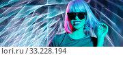 Купить «happy woman in wig and sunglasses over neon lights», фото № 33228194, снято 30 сентября 2019 г. (c) Syda Productions / Фотобанк Лори