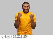 Купить «smiling african american man celebrating success», фото № 33228254, снято 15 декабря 2019 г. (c) Syda Productions / Фотобанк Лори