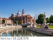 Square Prato della Valle, the canal with statues of prominent paduans and the Basilica of Santa Giustina. Padua, Italy (2017 год). Редакционное фото, фотограф Наталья Волкова / Фотобанк Лори