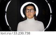 Купить «woman in glasses over white illumination on black», видеоролик № 33230738, снято 23 декабря 2019 г. (c) Syda Productions / Фотобанк Лори