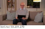 Купить «old man with tablet pc having video call at home», видеоролик № 33231270, снято 4 января 2020 г. (c) Syda Productions / Фотобанк Лори