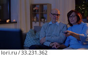 Купить «senior couple watching tv at home in evening», видеоролик № 33231362, снято 4 января 2020 г. (c) Syda Productions / Фотобанк Лори