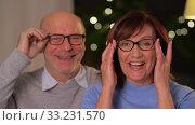 Купить «portrait of happy senior couple at home in evening», видеоролик № 33231570, снято 4 января 2020 г. (c) Syda Productions / Фотобанк Лори