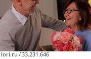 Купить «happy senior couple with bunch of flowers at home», видеоролик № 33231646, снято 20 января 2020 г. (c) Syda Productions / Фотобанк Лори