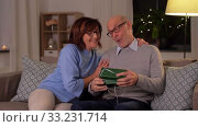 Купить «happy senior couple with gift box at home», видеоролик № 33231714, снято 20 января 2020 г. (c) Syda Productions / Фотобанк Лори