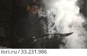 Купить «Blacksmith worker cooling out hot metal knife - steam comes off the blade», видеоролик № 33231986, снято 8 апреля 2020 г. (c) Константин Шишкин / Фотобанк Лори