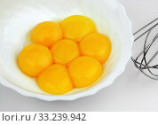A few yolks of eggs in a white bowl with a beater. Стоковое фото, фотограф Maryna Zaborina / PantherMedia / Фотобанк Лори