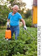 Man works with garden spray in the yard. Стоковое фото, фотограф Яков Филимонов / Фотобанк Лори