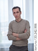 Portrait of Caucasian man with severe look and crossed arms sitting on windowsill in an apartment. Стоковое фото, фотограф Кекяляйнен Андрей / Фотобанк Лори