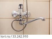 Bathroom water tap with long neck and shower hose, wall with beige tiles. Стоковое фото, фотограф Кекяляйнен Андрей / Фотобанк Лори