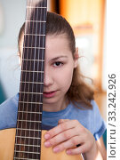 Купить «Portrait of teenage girl guitarist with fretboard of guitar, looking at camera», фото № 33242926, снято 7 февраля 2020 г. (c) Кекяляйнен Андрей / Фотобанк Лори