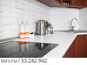 Electric stove with glass touch cook surface, teapot and stainless sink are in kitchen interior, white tabletop with stone splash back. Стоковое фото, фотограф Кекяляйнен Андрей / Фотобанк Лори