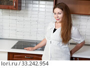 Cheerful Caucasian woman standing next to electric touch stove mounted in white tabletop in domestic kitchen. Стоковое фото, фотограф Кекяляйнен Андрей / Фотобанк Лори