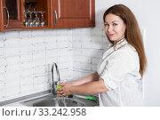 Happy Caucasian woman washes green apple in sink in domestic kitchen, smiling housewife portrait. Стоковое фото, фотограф Кекяляйнен Андрей / Фотобанк Лори