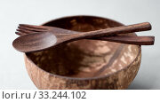 Купить «close up of coconut bowl, wooden spoon and fork», видеоролик № 33244102, снято 5 июля 2020 г. (c) Syda Productions / Фотобанк Лори