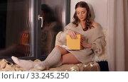 Купить «woman opening christmas gift at home at night», видеоролик № 33245250, снято 21 января 2020 г. (c) Syda Productions / Фотобанк Лори