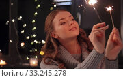 Купить «happy young woman with sparklers at home», видеоролик № 33245278, снято 21 января 2020 г. (c) Syda Productions / Фотобанк Лори
