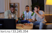 Купить «happy male friends with beer eating pizza at home», видеоролик № 33245354, снято 12 января 2020 г. (c) Syda Productions / Фотобанк Лори