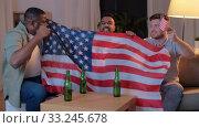 Купить «friends with american flag watching tv at night», видеоролик № 33245678, снято 13 января 2020 г. (c) Syda Productions / Фотобанк Лори