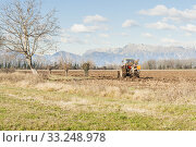 Agricultural landscape with tractor plowing. Стоковое фото, фотограф Franco Nadalin / PantherMedia / Фотобанк Лори
