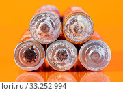 Купить «Multiple used bad AA alkaline batteries are seen arranged in a pile on a reflective orange surface. Closeup front view from the plus side of the battery.», фото № 33252994, снято 16 июля 2020 г. (c) age Fotostock / Фотобанк Лори