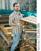 Купить «Man repairs wooden pallets in the backyard of a country house», фото № 33260086, снято 28 февраля 2019 г. (c) Яков Филимонов / Фотобанк Лори