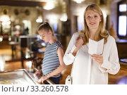 Woman looking at guidebook in museum of arts, girl on background. Стоковое фото, фотограф Яков Филимонов / Фотобанк Лори