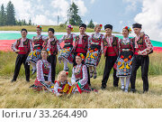 Купить «Rozhen, Bulgaria - July 15, 2016: Bulgarian dancers in folklore costumes areposign for a picture in front of the Bulgarian flag before going on stage for their dance performance.», фото № 33264490, снято 15 июля 2016 г. (c) age Fotostock / Фотобанк Лори