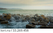 Бушующие волны разбиваются против скалистого берега в шторм. Море брызг и пены. Стоковое фото, фотограф Сергей Тиняков / Фотобанк Лори