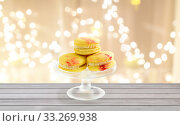 Купить «yellow macaroons on glass confectionery stand», фото № 33269938, снято 6 июля 2018 г. (c) Syda Productions / Фотобанк Лори