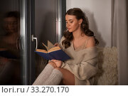 Купить «woman reading book sitting at window at home», фото № 33270170, снято 19 января 2020 г. (c) Syda Productions / Фотобанк Лори