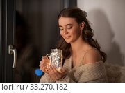 woman with garland lights in glass mug at home. Стоковое фото, фотограф Syda Productions / Фотобанк Лори